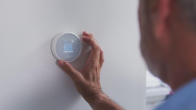 kıdemli i̇spanyol adam evde dijital merkezi isıtma termostat ayarlama - ayarlamak stok videoları ve detay görüntü çekimi