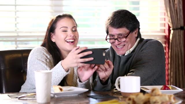 vídeos de stock e filmes b-roll de senior hispanic man and daughter looking at smart phone - old men window