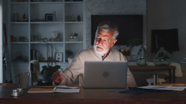 senior hispanic man checking his finances online at home using a laptop computer at night, close up - online banking video stock e b–roll