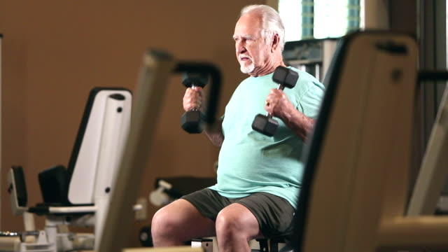 Senior Hispanic man exercising at gym, lifting weights A senior Hispanic man in his 80s exercising at the gym, lifting dumbbells in his hands, looking away with a serious expression. health club stock videos & royalty-free footage