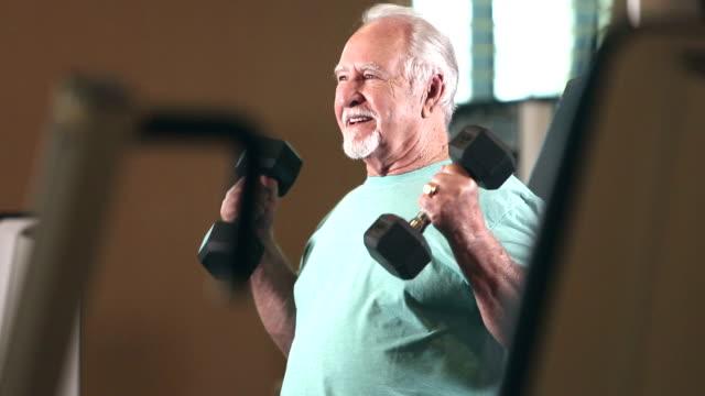 senior-hispanic mann training im fitness-studio, gewichte zu heben - gewichtstraining stock-videos und b-roll-filmmaterial