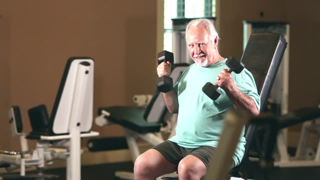 senior hispanic man exercising at gym, lifting weights - baffo peluria del viso video stock e b–roll