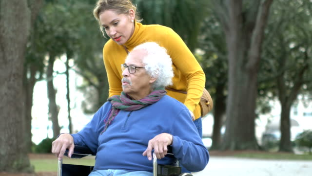 Senior Hispanic man in wheelchair, with adult daughter A senior Hispanic man in his 80s sitting in a wheelchair, taking a walk in the park with his adult daughter, a mid adult woman in her 30s. pushing wheelchair stock videos & royalty-free footage