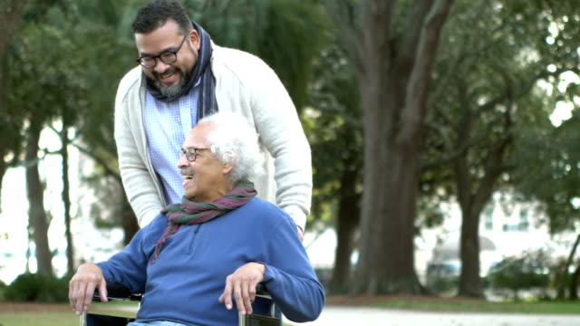 Senior Hispanic man in wheelchair, with adult son A senior Hispanic man in his 80s sitting in a wheelchair, taking a walk in the park with his adult son, a mid adult man in his 30s. affectionate stock videos & royalty-free footage