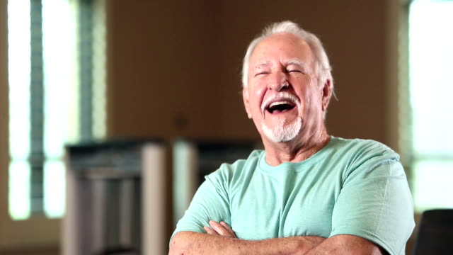 senior hispanic man looking at camera, smiling, laughing - baffo peluria del viso video stock e b–roll