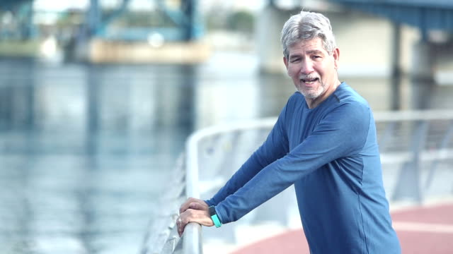 Senior Hispanic man on city waterfront A senior Hispanic man in his 60s standing on a city waterfront, looking at the view with a serious expression. He turns to look at the camera and smiles. railing stock videos & royalty-free footage