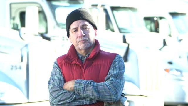 vídeos y material grabado en eventos de stock de camionero hispano senior de pie por fila de semi-camiones - conductor de autobús
