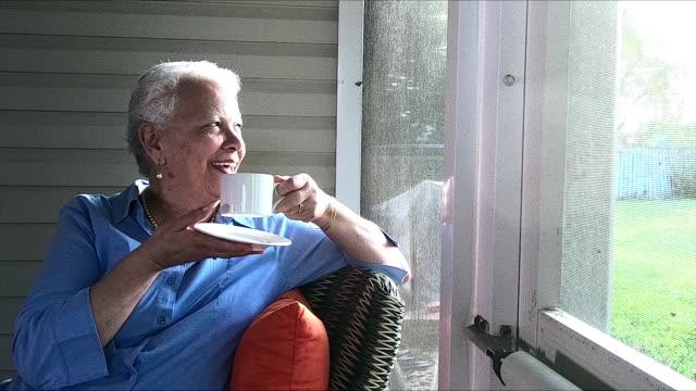 senior hispanic woman enjoying cup of tea or coffee - portico video stock e b–roll
