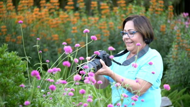 Senior Hispanic woman in park photographing flowers