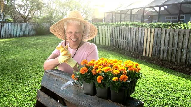 vidéos et rushes de femme senior hispanique, mettre des gants de jardinage - senior dynamique