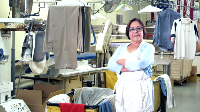 Senior Hispanic woman working at dry cleaners A senior Hispanic woman in her 60s working at the dry cleaners. She is standing next to a cart of laundry in the back room, looking at the camera. She is an employee, or perhaps the owner of this small business. laundry basket stock videos & royalty-free footage
