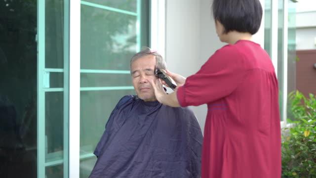 senior home haarschnitt, tochter schnitt ihrem vater die haare zu hause in coronavirus covid-19 pandemie - friseur lockdown stock-videos und b-roll-filmmaterial