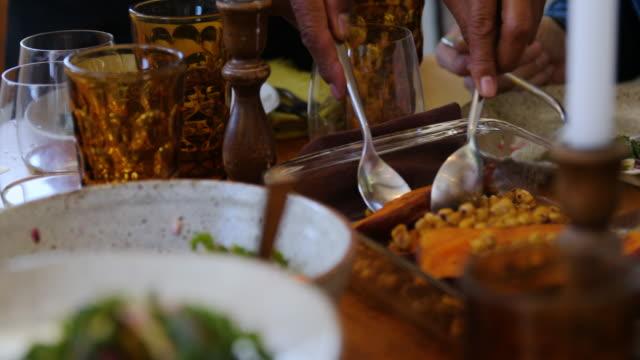 vídeos de stock, filmes e b-roll de anfitrião sênior que sere a batata doce roasted ao convidado - vegetarian meal