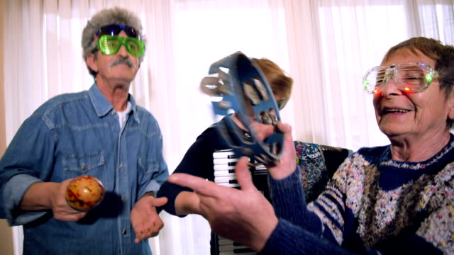 Senior house party Senior peoples having party at home. One woman is playing accordion and the other woman and man dancing with tambourine. party stock videos & royalty-free footage