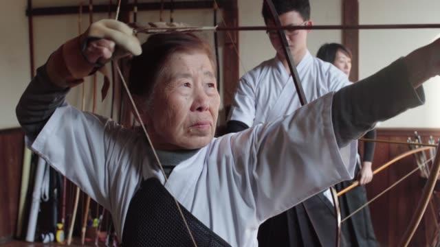 彼女の矢を nocking し、彼女のショットを取るシニア日本の射手 - シニア点の映像素材/bロール