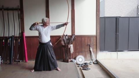 vidéos et rushes de archer japonais aîné prenant l'objectif et perdant sa flèche - arts martiaux