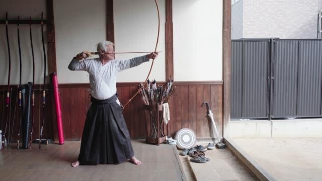 Senior Japanese archer taking aim and loosing his arrow Senior Japanese archer taking aim and loosing his arrow. Shot in 4K. Okayama, Japan. 2019 martial arts stock videos & royalty-free footage