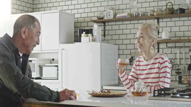 台所でアフタヌーンティーブレイクを楽しむ日本のシニアカップル - 老夫婦点の映像素材/bロール
