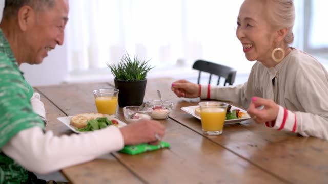 朝食と会話を楽しむシニア日本人カップル - ヘルシーなライフスタイル点の映像素材/bロール