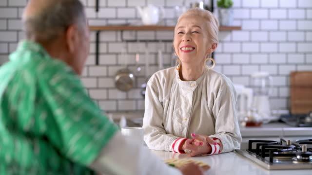 キッチンカウンターで朝食を楽しむシニア日本人カップル - 対面点の映像素材/bロール