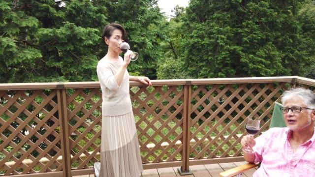飲み物を飲みながら家で時間を楽しむシニア日本人カップル - デッキ点の映像素材/bロール