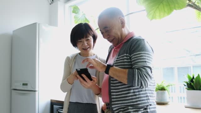 スマート フォンで遊ぶ日本のシニアのカップル - シニア点の映像素材/bロール