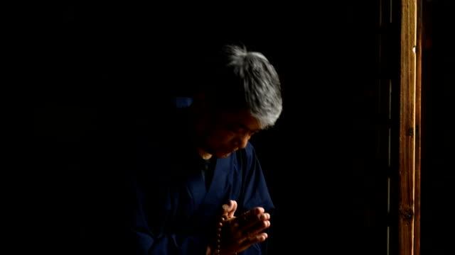 Senior Japanese man praying at a temple video