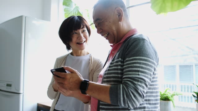 Senior Japanese Man Showing Smart Phone to Wife video