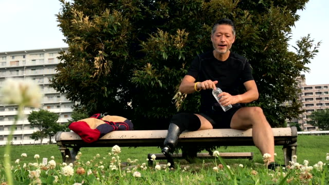 senior japanese man with a prosthetic leg resting after his fitness routine - acqua potabile video stock e b–roll