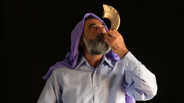 старший еврейский человек играет шофар на религиозный праздник - rosh hashana стоковые видео и кадры b-roll