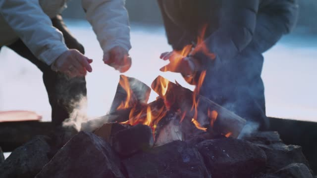 senior ladies warming themselves by a fire - ice on fire video stock e b–roll