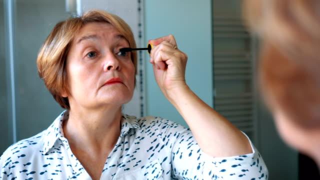 Senior lady applying mascara Senior lady applying mascara in front of the mirror in the bathroom. mascara stock videos & royalty-free footage