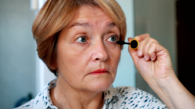 Ältere Dame, die Wimperntusche auftragen – Video