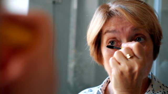 Senior lady applying mascara Close-up video of senior lady applying mascara in front of the mirror in the bathroom. mascara stock videos & royalty-free footage