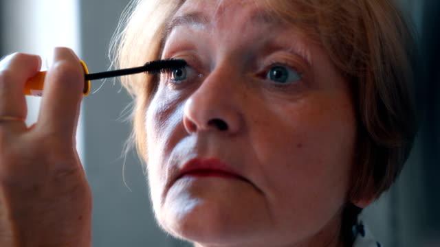 Senior lady applying mascara video