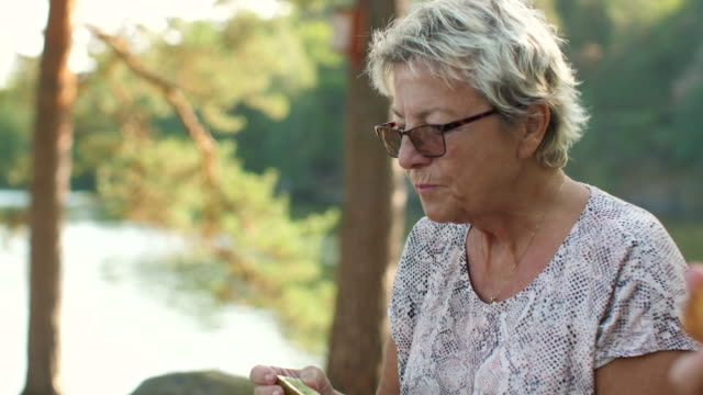 Senior Lady having a picnic in a forest A senior woman is having a picnic in a forest during summer. She is eating a pickle. pickle stock videos & royalty-free footage