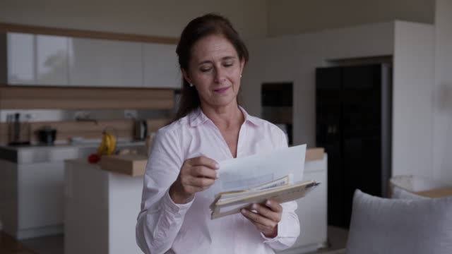 Senior latin american woman at home checking her mail Senior latin american woman at home checking her mail - Lifestyles post office stock videos & royalty-free footage