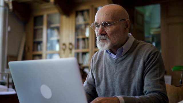 senior lawyer male researcher in round glasses and grey pulover working - usare il laptop video stock e b–roll