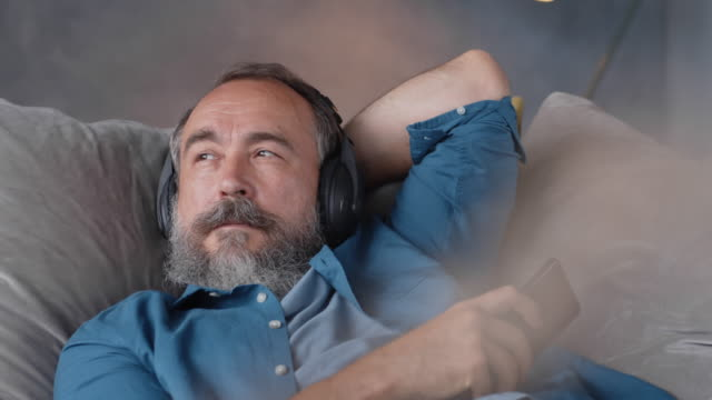 vidéos et rushes de senior listening to music sur canapé - podcasting