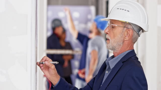 Senior male architect writing on the whiteboard at the building site