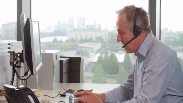 Senior male call centre worker wearing headset, side view video