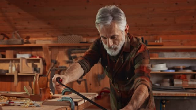 Senior male carpenter using a drawknife in his workshop