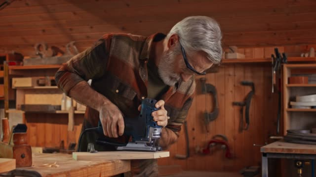 Senior male carpenter using a jigsaw to cut a piece of wood in his workshop