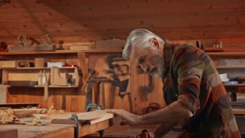 atölyesinde bir uçak kullanan kıdemli erkek marangoz - abd dışı yer stok videoları ve detay görüntü çekimi
