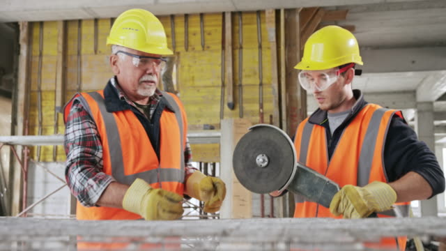 senior männlich erdarbeiter lehrt einen männlichen lehrling, wie man durch stahlgitter schneiden - kreissäge stock-videos und b-roll-filmmaterial