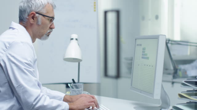 senior male laboratory researcher working with graphs on his personal computer. his assistant works at his desk in the background. - servizi video stock e b–roll