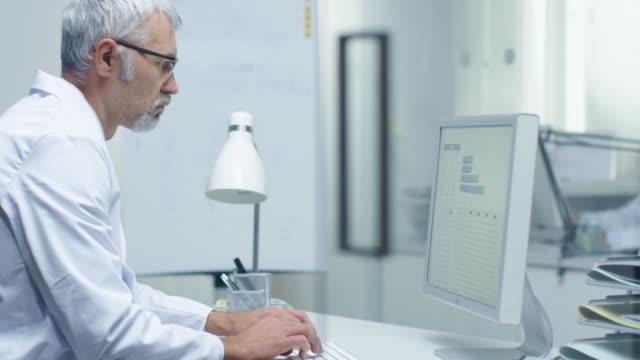 senior manliga laboratorie forskare arbeta med grafer på sin dator. hans assistent arbetar vid hans skriv bord i bakgrunden. - looking inside inside cabinet bildbanksvideor och videomaterial från bakom kulisserna