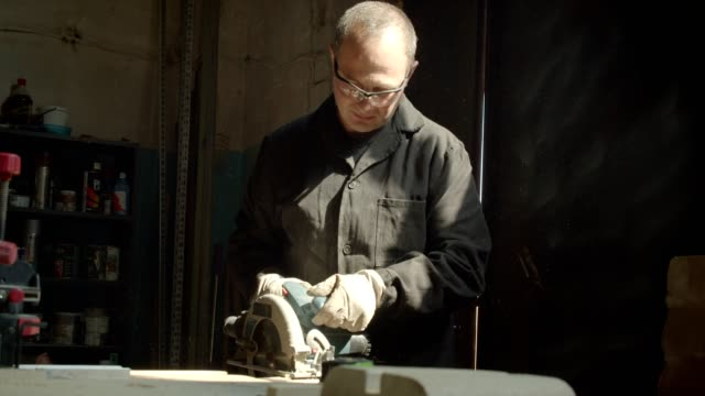 Senior male master working at wood factory grinding with headsaw the wooden board. Senior male master working at wood factory grinding with headsaw the wooden board power tool stock videos & royalty-free footage