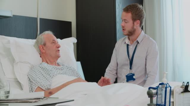 senior männlichen patienten und arzt sprechen in krankenhaus-zimmer - männliches tier stock-videos und b-roll-filmmaterial