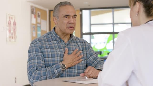 vídeos de stock e filmes b-roll de senior male patient getting medical exam - ataque cardíaco